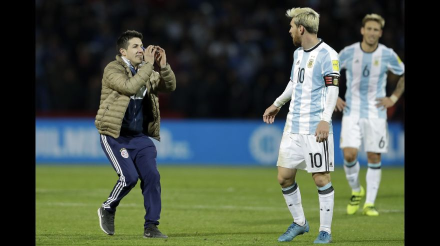 A fan who invaded the pitch gestures to Argentina's Lionel Messi, center, during a 2018 World Cup qualifying soccer match against Uruguay in Mendoza, Argentina, Thursday, Sept. 1, 2016.(AP Photo/Victor R. Caivano)