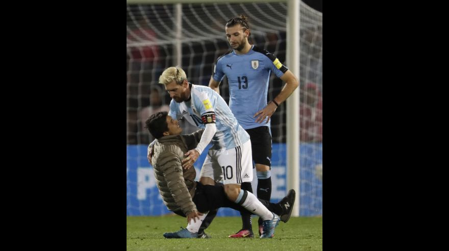Argentina's Lionel Messi holds a fan who entered the field to touch him during a 2018 World Cup qualifying soccer match against Uruguay in Mendoza, Argentina, Thursday, Sept. 1, 2016.(AP Photo/Natacha Pisarenko)