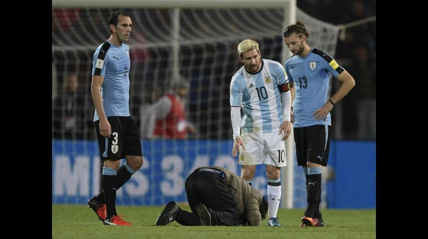 A fan tries to kiss the feet of Argentina's Lionel Messi during the Russia 2018 World Cup qualifier football match against Uruguay in Mendoza, Argentina, on September 1, 2016. / AFP / JUAN MABROMATA