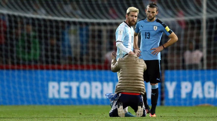 Football Soccer - World Cup 2018 Qualifiers - Argentina v Uruguay - Estadio Malvinas Argentinas, Mendoza, Argentina - 01/09/16 - A fan who jumped onto the field kneels to touch Argentina's Lionel Messi while Uruguay's Gaston Silva (R) looks on. REUTERS/Marcos Brindicci