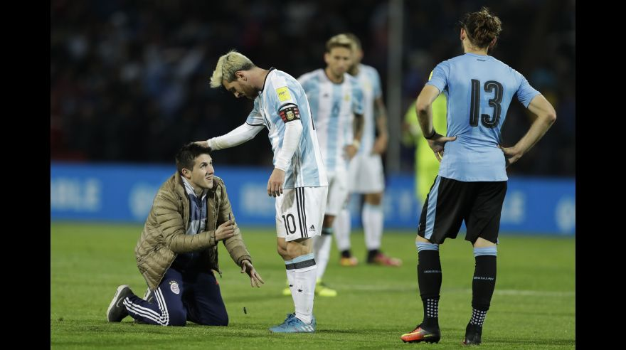 A fan who invaded the pitch kneels in front of Argentina's Lionel Messi, center, as Uruguay's Gaston Silva looks on during a 2018 Russia World Cup qualifying soccer match in Mendoza, Argentina, Thursday, Sept. 1, 2016.(AP Photo/Victor R. Caivano)