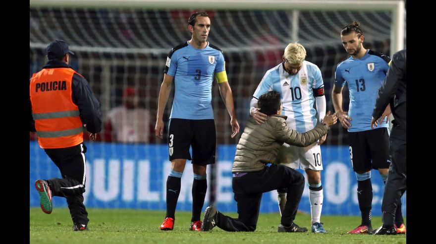 Football Soccer - World Cup 2018 Qualifiers - Argentina v Uruguay - Estadio Malvinas Argentinas, Mendoza, Argentina - 01/09/16 - A fan who jumped onto the field kneels to touch Argentina's Lionel Messi while Uruguay's Gaston Silva (R) and Diego Godin look on. REUTERS/Marcos Brindicci
